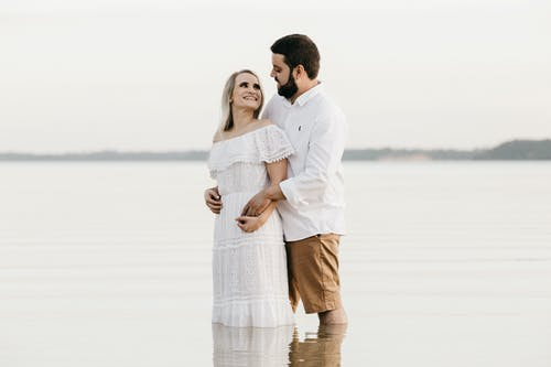 Side view of bearded male embracing smiling female beloved in elegant dress while standing in sea and looking at each other during vacation