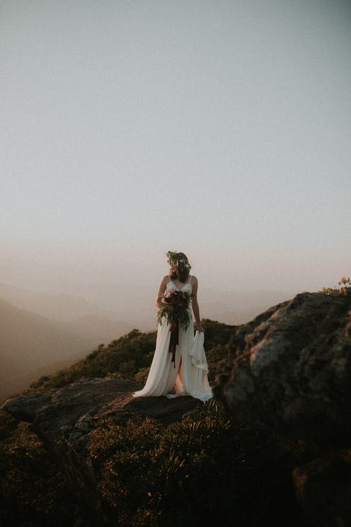 Woman in White Wedding Gown Standing on Brown Rock Formation