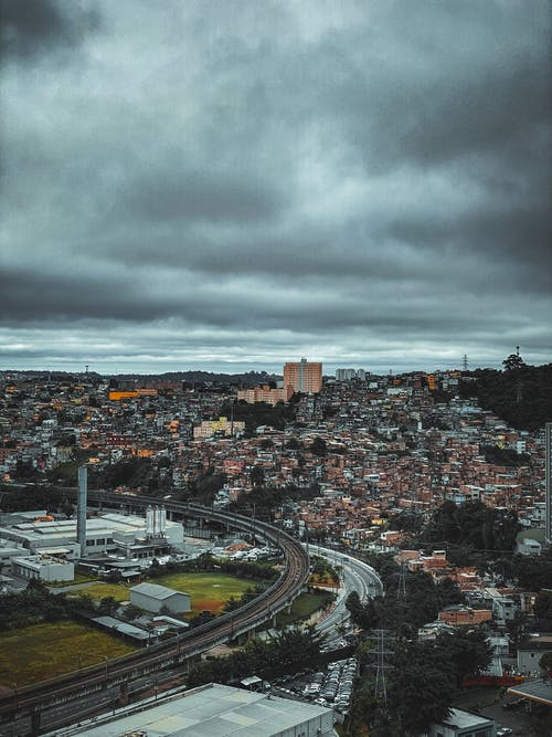Cityscape with modern buildings under cloudy sky in overcast weather
