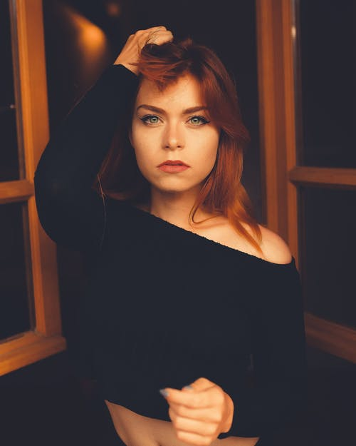 Young sensitive female in trendy black clothes standing with raised arm while looking at camera at home