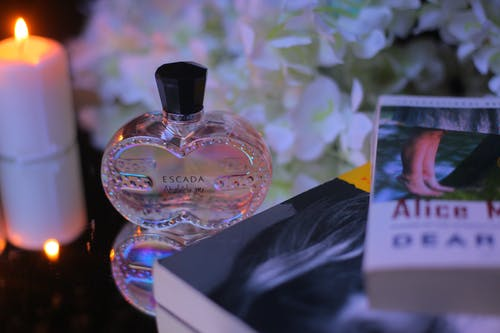 From above of ornamental bottle of aromatic perfume near bright candle and books behind blooming flowers at home