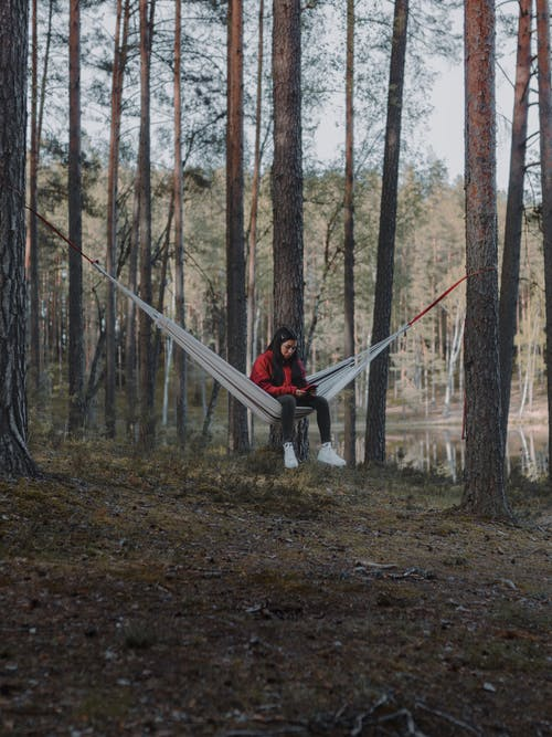 Woman Sitting in a Hammock in a Forest