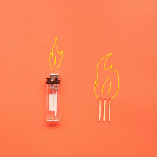 Cigarette lighter and matches placed on orange background