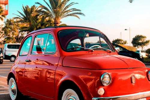 Vintage small red car parked on roadside near tropical palm trees against cloudless blue sky