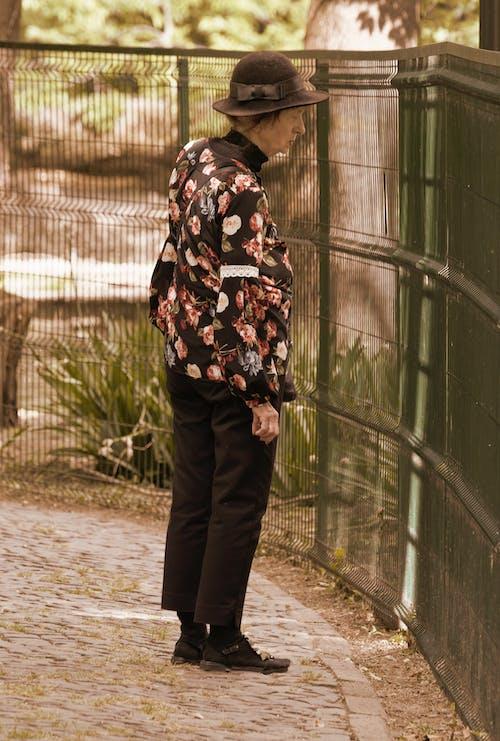 Gratis lagerfoto af gammel kvinde, metal hegn, se, Sepia