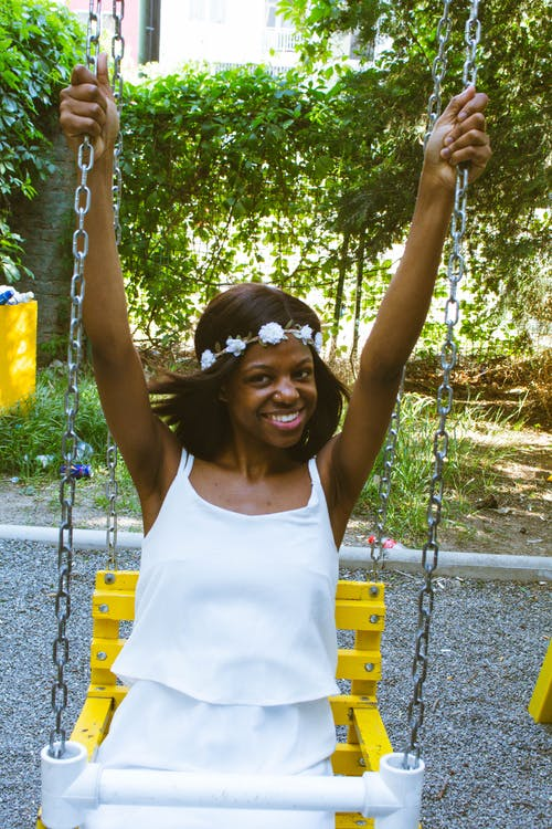 Happy ethnic lady swinging in amusement park