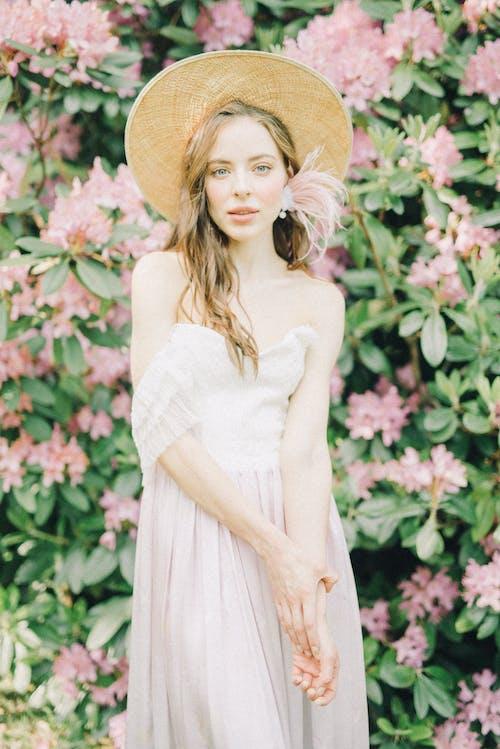 白色無袖連衣裙,戴著棕色太陽帽子站在粉紅色的花朵附近的女人