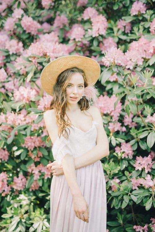 穿棕色太陽帽子站在粉紅色的花朵附近的白色連衣裙的女人