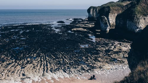 From above of blue ocean surrounded with rocky cliffs at low tide at Selwicks Bay in Flamborough