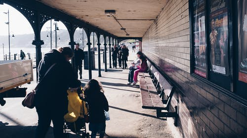 People Sitting on Bench Near Train Rail