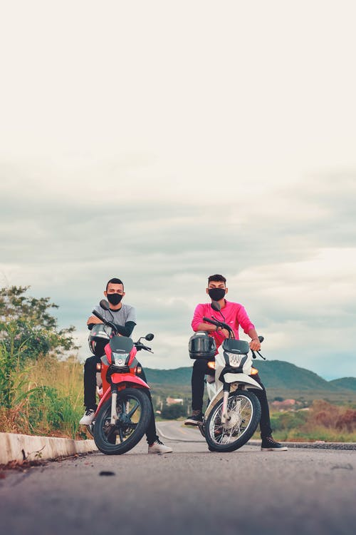 Full body of anonymous young male friends in casual clothes and face masks sitting on modern motorcycles on asphalt road