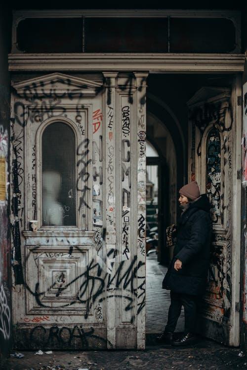 Man in Black Coat Standing in Front of White and Brown Floral Door