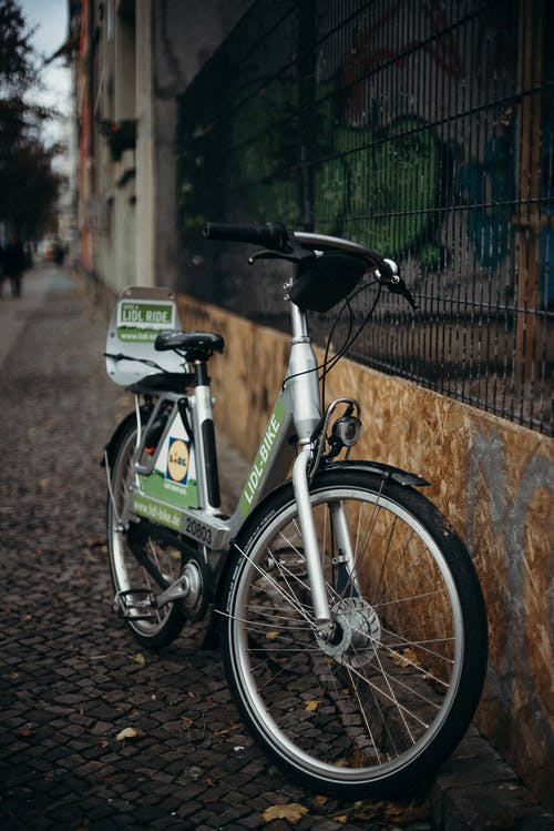 Green and Black Bicycle Beside Brown Brick Wall