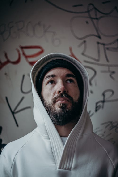 Man in White Hoodie Wearing Black and White Knit Cap