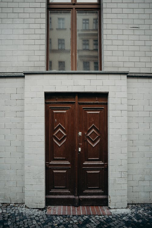 Red Wooden Door on White Concrete Building