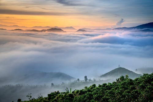 Breathtaking landscape of thick clouds floating over mountains with lush green tropical foliage at sundown