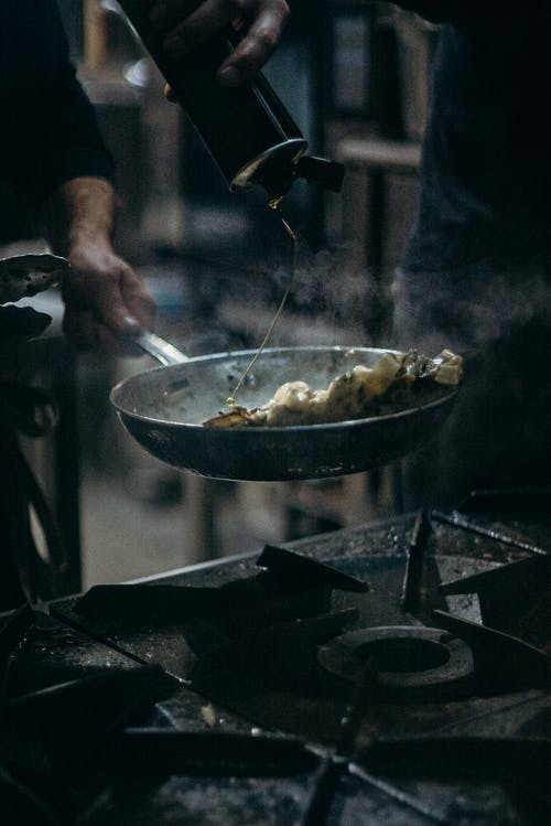 Person Cooking Food on Stainless Steel Bowl