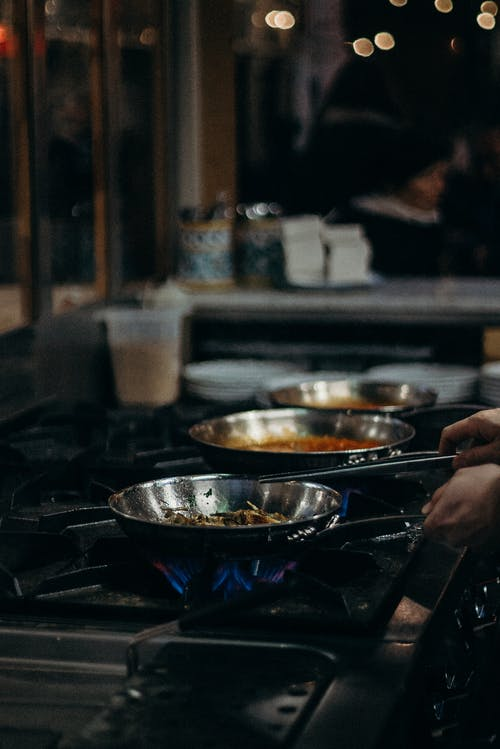 Person Cooking on Stainless Steel Bowl
