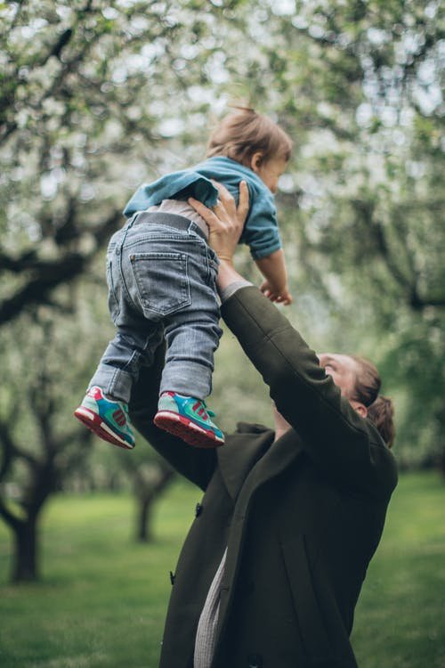 Man in Brown Pants Carrying Child in Blue Denim Jacket