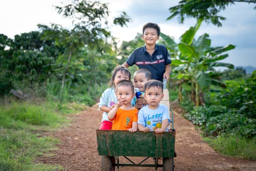 Happy Asian kids having fun together in countryside
