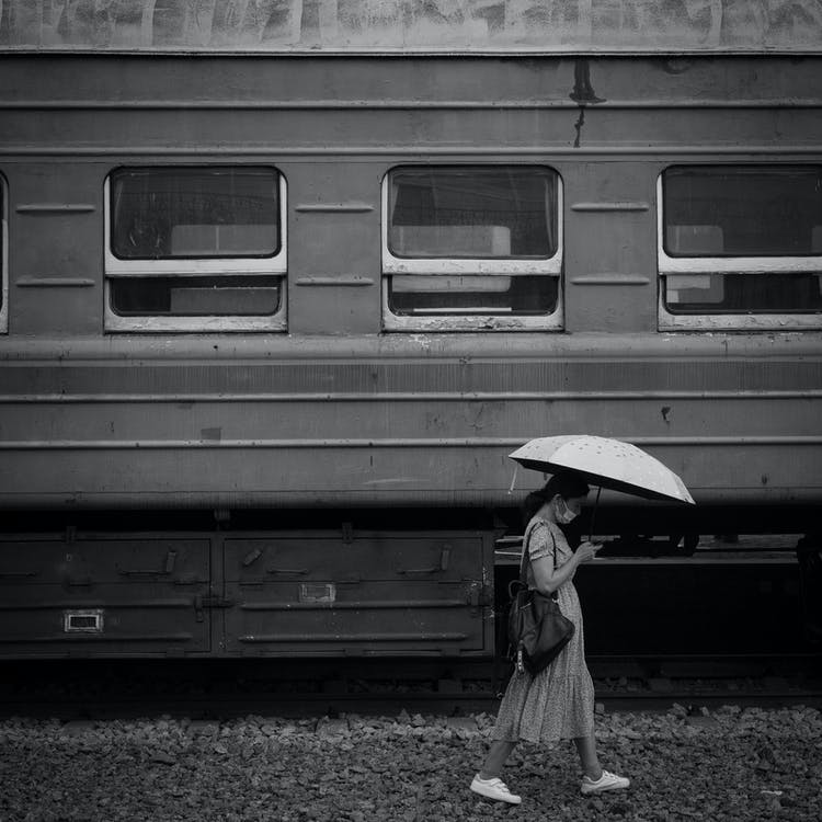 Black and white old train on railway and female in casual wear with backpack wearing face mask walking under umbrella