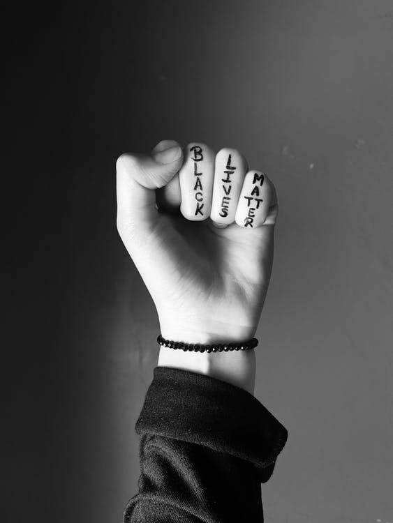 Grayscale Photo of Persons Fist