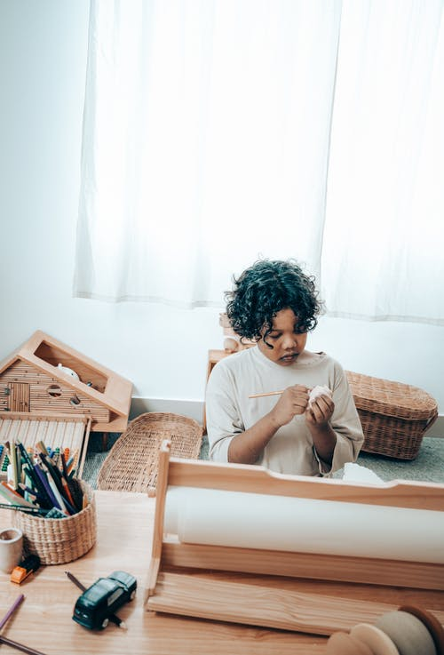 Black girl drawing on piece of paper sitting at table