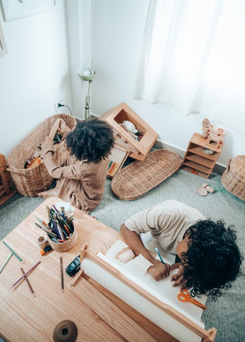 Top view of anonymous African American child drawing on paper sheet with pencil while sitting near barefoot sister playing with toys put in wicker basket in flat