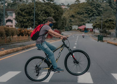 Man in face mask riding bicycle on crossing