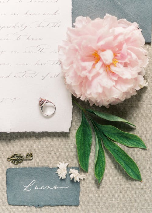 Ring on Top of Letter Beside Pink Flower