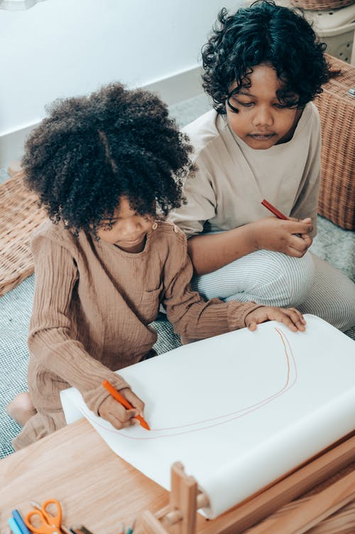 From above of pensive African American girl drawing with felt pen on large sheet of paper while sitting near sister at wooden table in flat