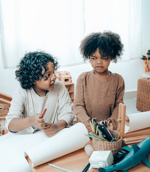 Discontented African American girl sitting with sister near paper sheets