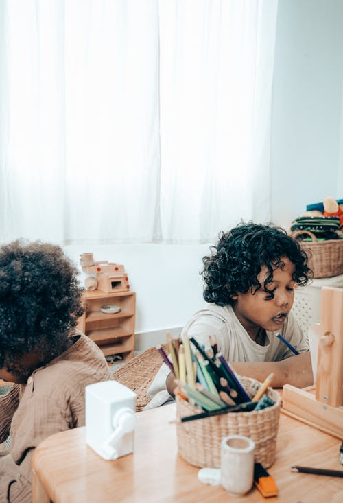 Black kid drawing near crop unrecognizable sister sitting in apartment