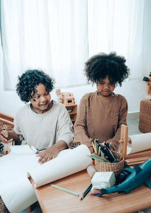 High angle of happy black children in casual wear sitting at wooden table with paper sheets and assorted pencils in wicker vase in apartment