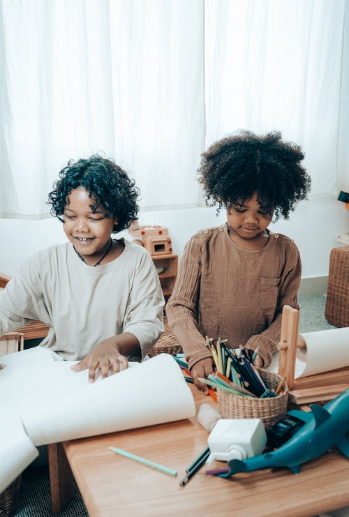 Happy black children sitting at table with paper sheets
