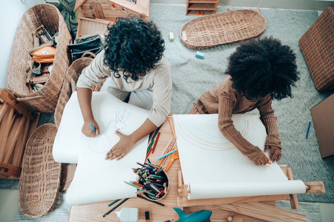 Faceless African American siblings drawing on blank papers at home