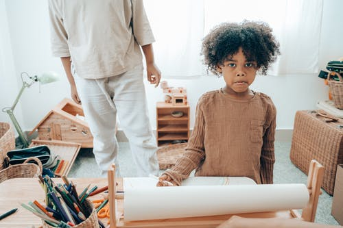 Modest black kid in casual clothes sitting at table with stationery and paper close to faceless sibling and looking at camera