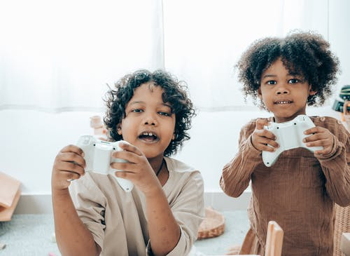 Cheerful black children playing with game pads in room