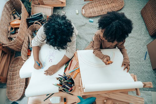 Top view of anonymous African American kids drawing on blank paper using pencil while sitting at table with paper roll at home
