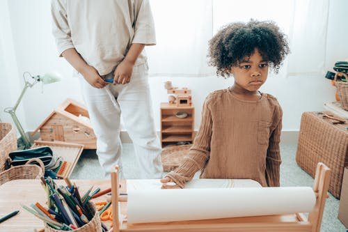 Sad African American kid with paper sheet near crop sibling