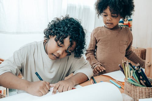 Focused black girl drawing with pencil on paper sheet while sitting at wooden table with stationery near crop adorable sister in living room