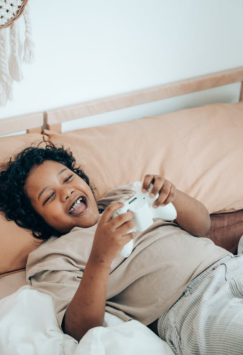 Excited black kid using joystick in bed