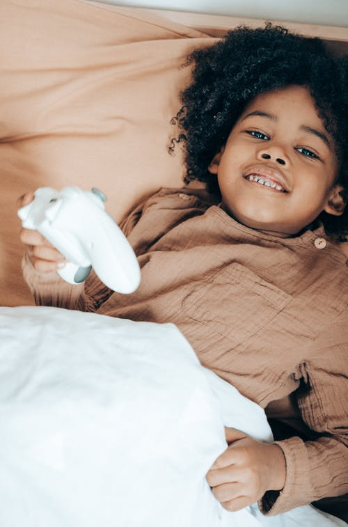 From above of smiling little African American child in sleepwear lying in cozy bed and using gamepad while spending free time at home and looking at camera
