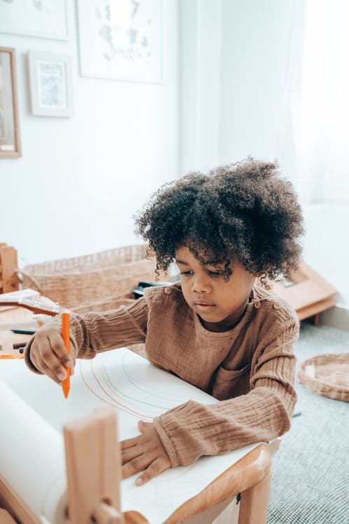 Cute focused African American girl in domestic clothes sitting at wooden table and drawing with marker on paper sheet while spending free time in modern apartment
