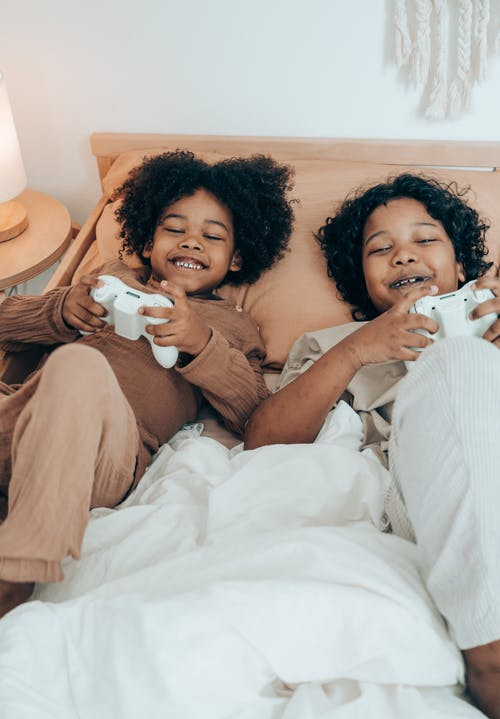 Cheerful black kids resting on bed in morning