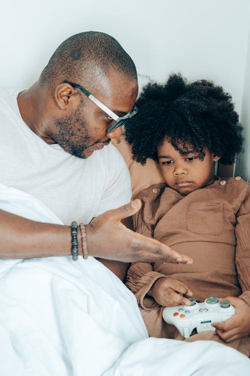 Black father speaking with child at home
