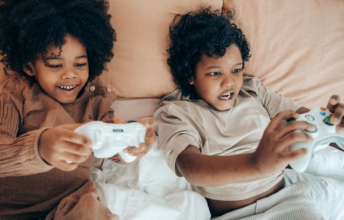 Happy ethnic siblings playing with gamepad at home