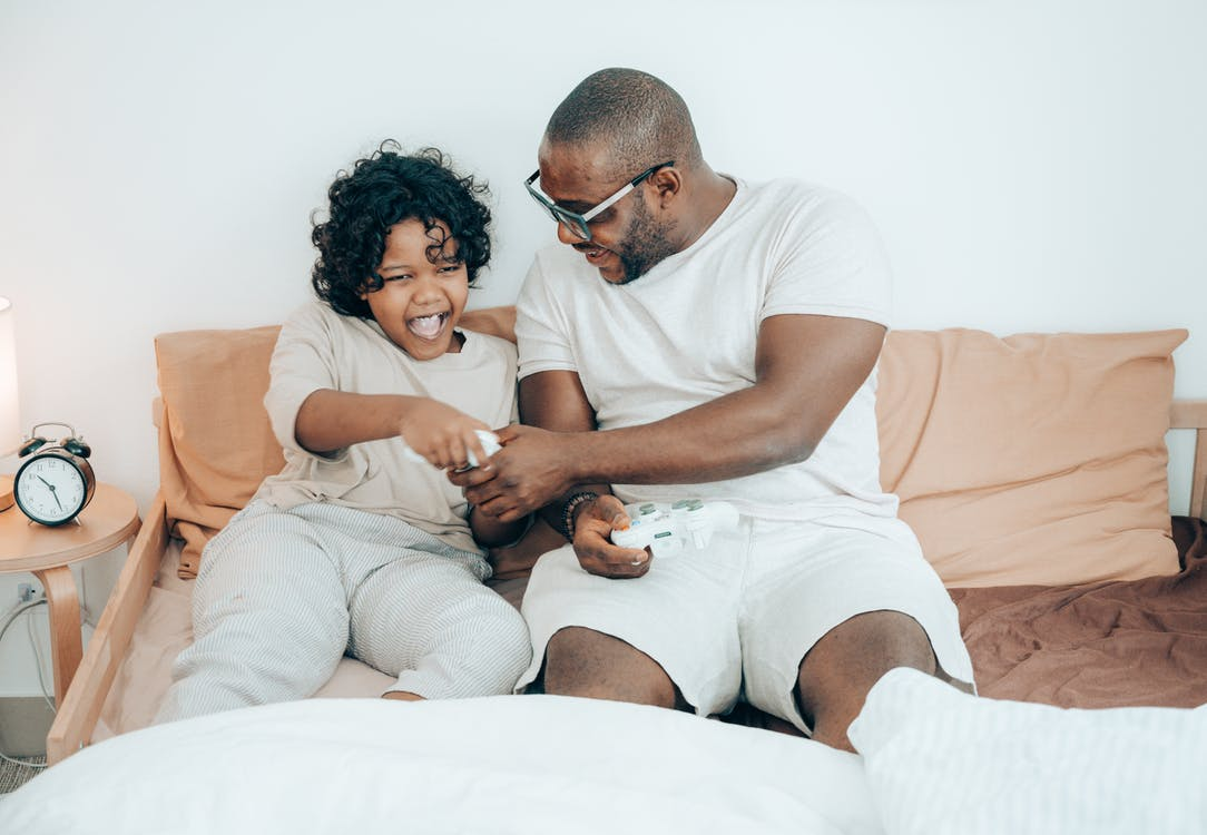 Black father and kid using joysticks on bed