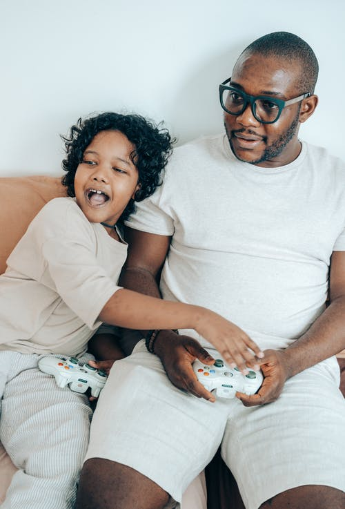 From above of cheerful young man in glasses with kid enjoying play on game console while relaxing together on sofa in cozy apartment