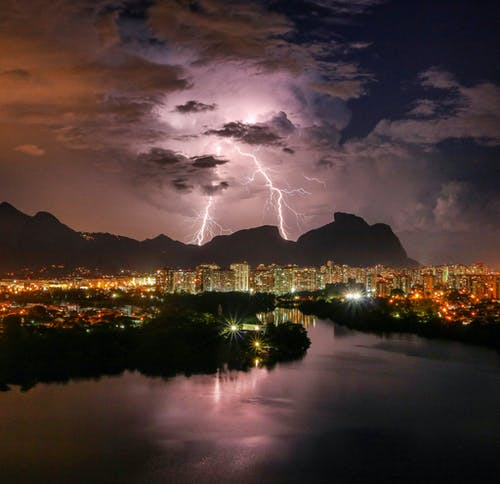 Picturesque view of bright lightning in gloomy sky above city buildings near river and mountains during thunderstorm at night